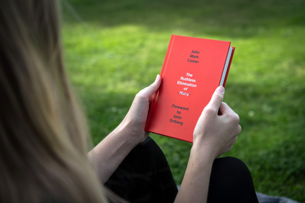 person holding red book during daytime