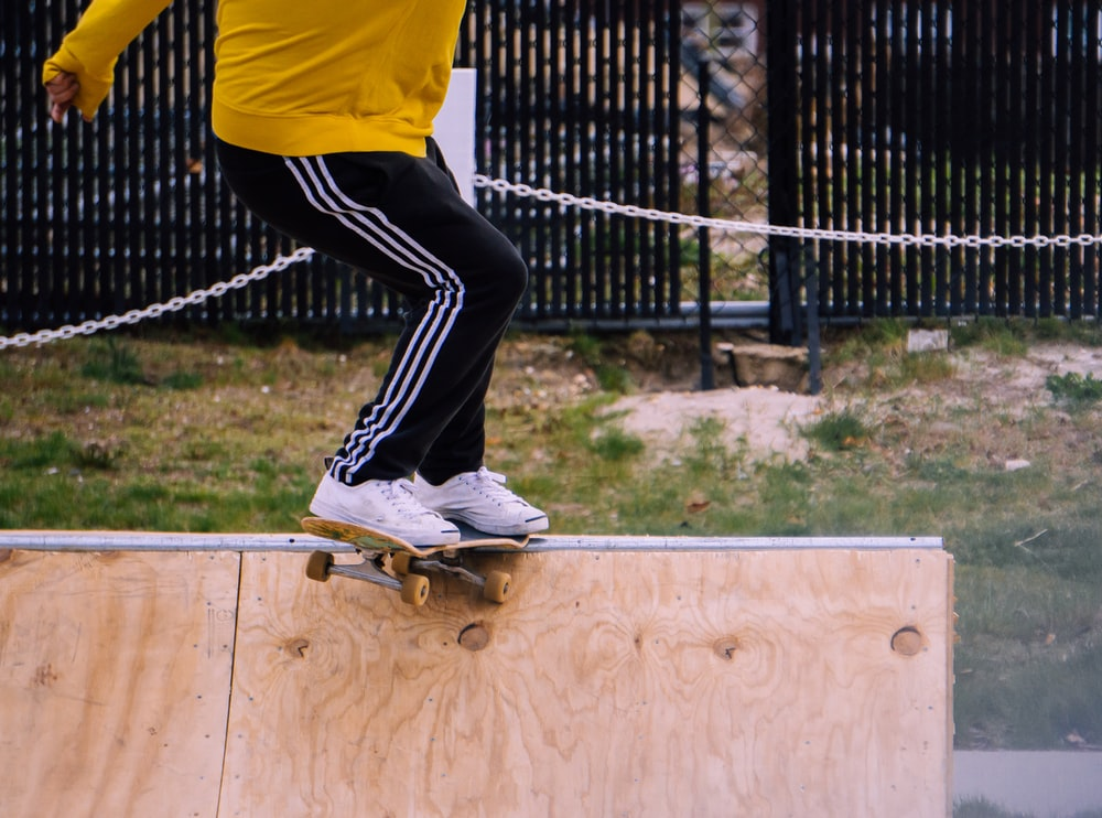 person in yellow shirt and black pants wearing white sneakers jumping on trampoline