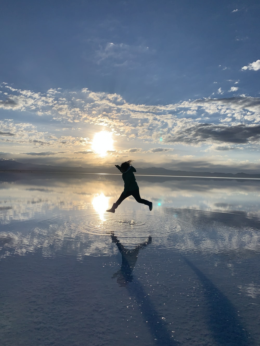 woman in black jacket and pants jumping on snow covered ground under blue and white cloudy