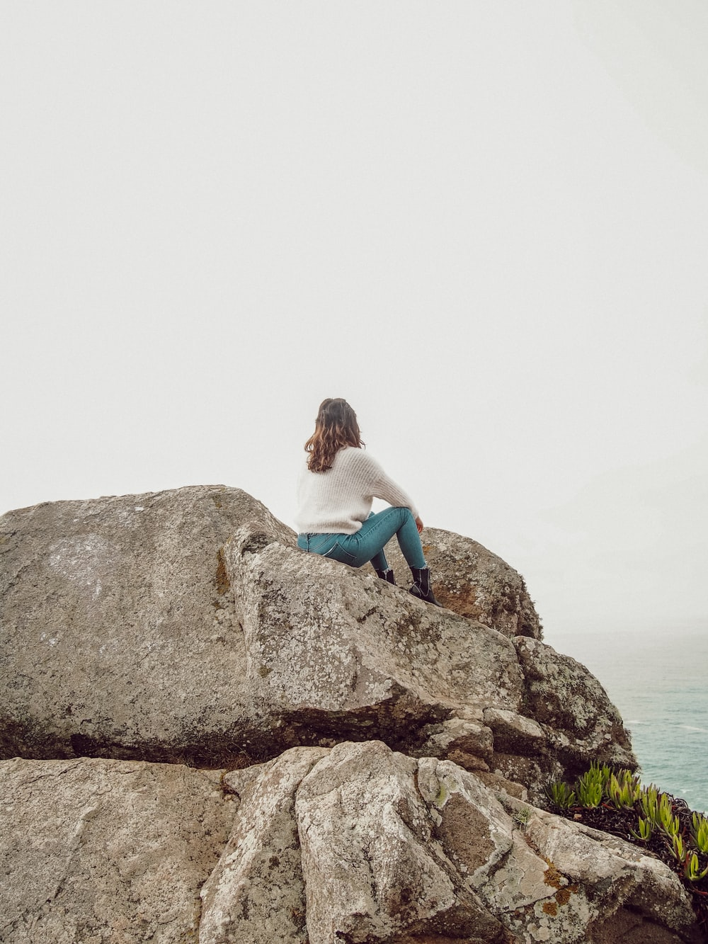 woman in blue tank top and blue denim jeans sitting on brown rock formation during daytime