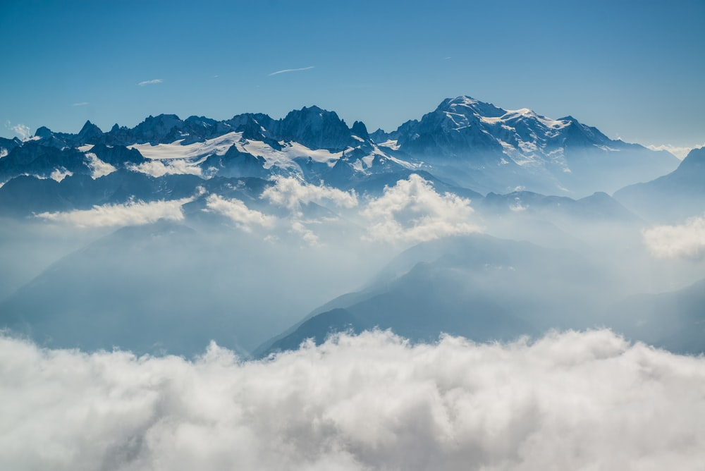 snow covered mountains under white clouds during daytime