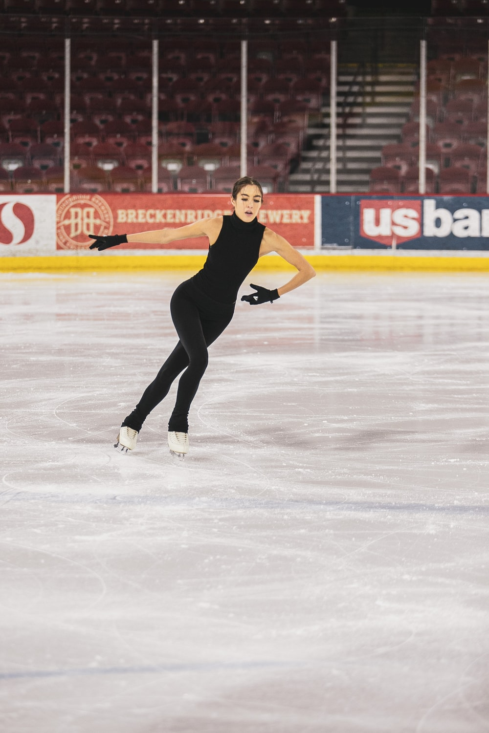 woman in black tank top and black pants playing ice hockey