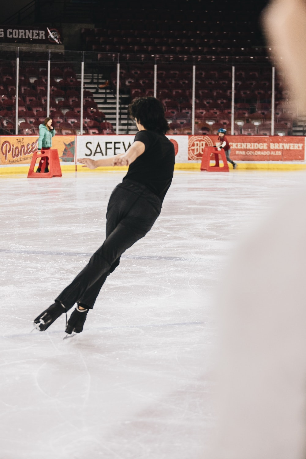 man in black pants and red shirt playing ice hockey
