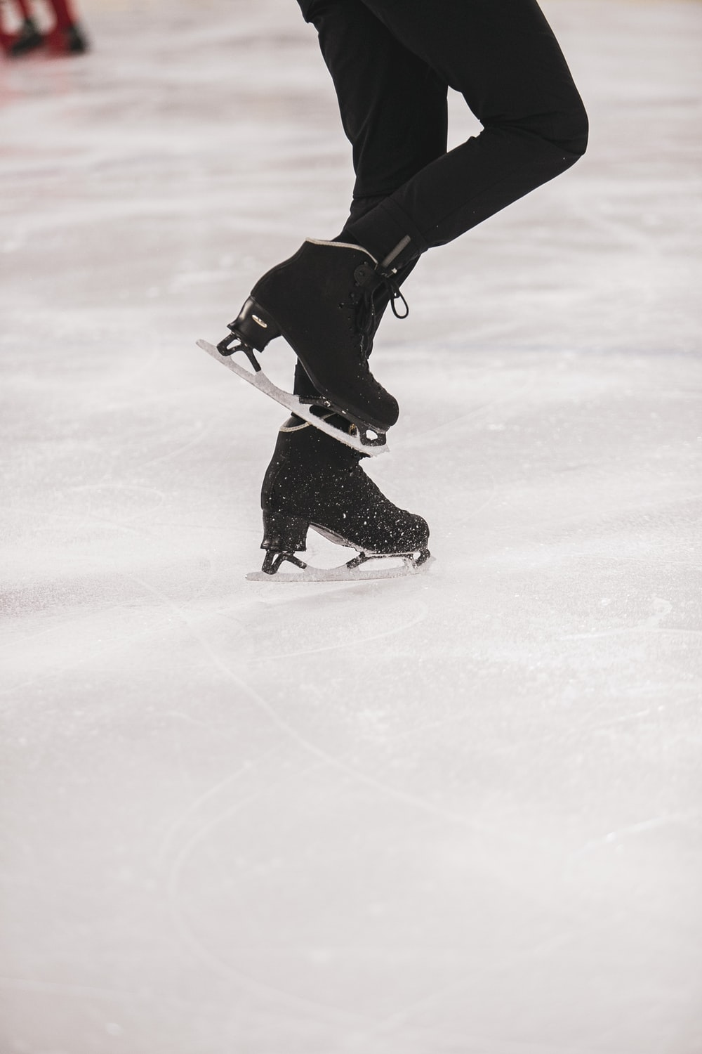 person in black jacket and black pants playing ice hockey