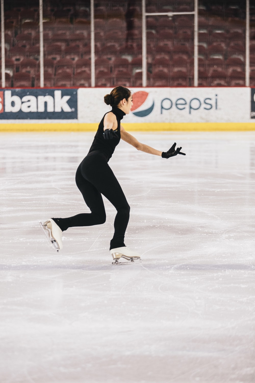 woman in black tank top and black pants doing ice skating