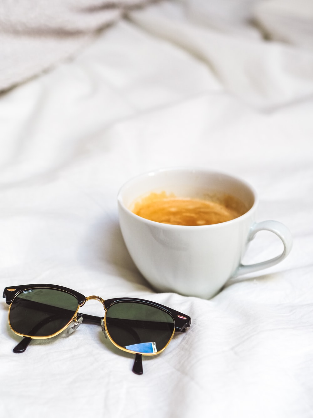 brown sunglasses beside white ceramic cup on white textile