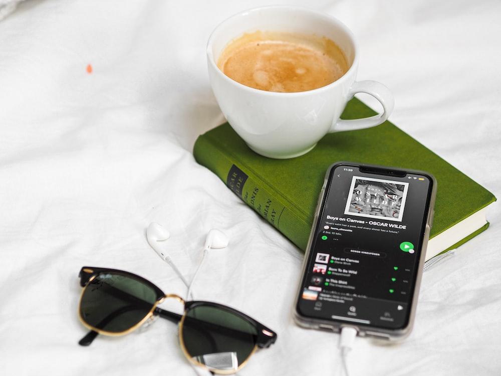 black iphone 5 beside white ceramic mug on white table