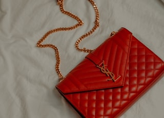 red leather sling bag on white textile