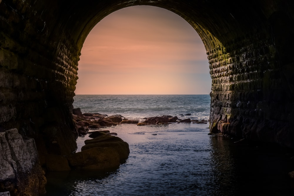 brown arch on sea shore during daytime