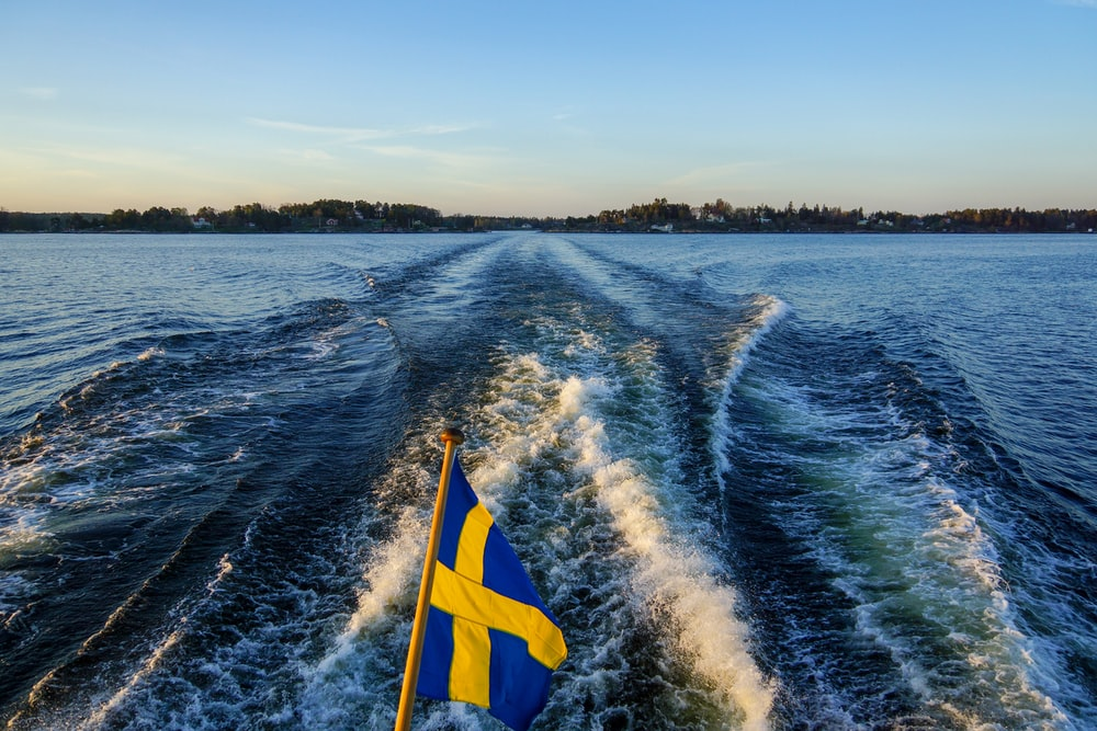 blue and yellow flag on body of water during daytime
