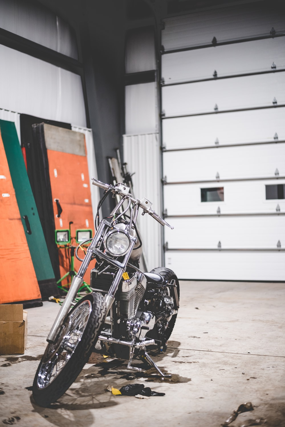 black motorcycle parked beside orange and white wall