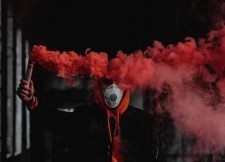 man in black suit holding red smoke