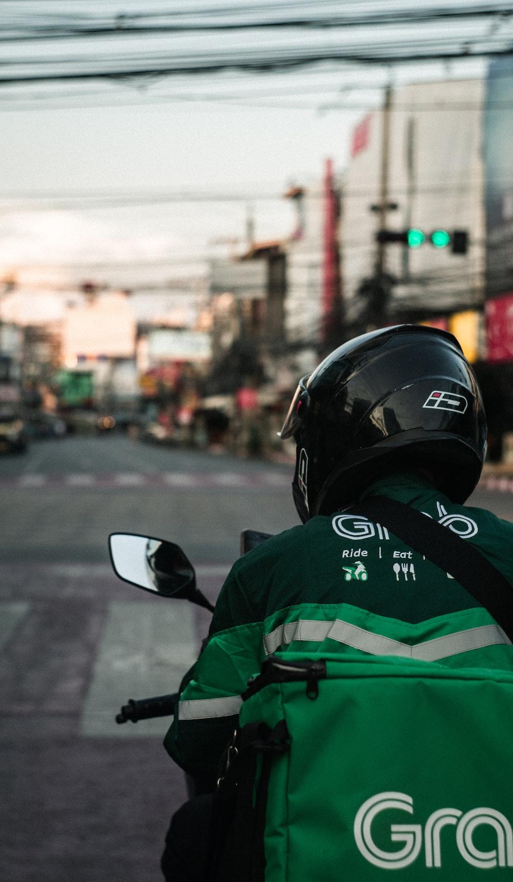 man in green and black jacket wearing black helmet