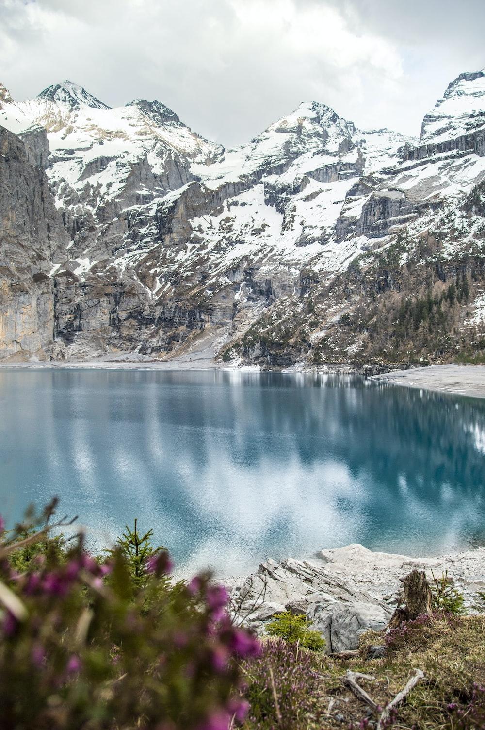 blue lake between gray rocky mountains during daytime