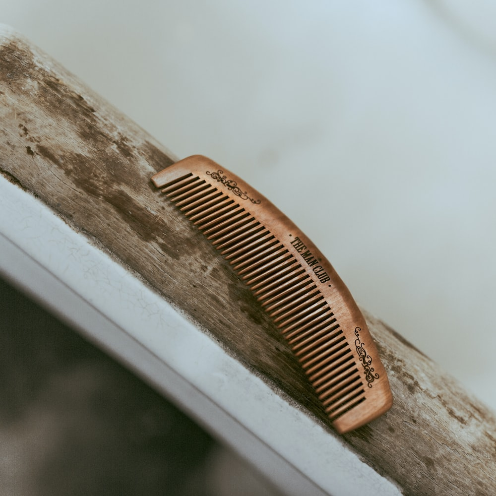brown hair comb on white wooden table