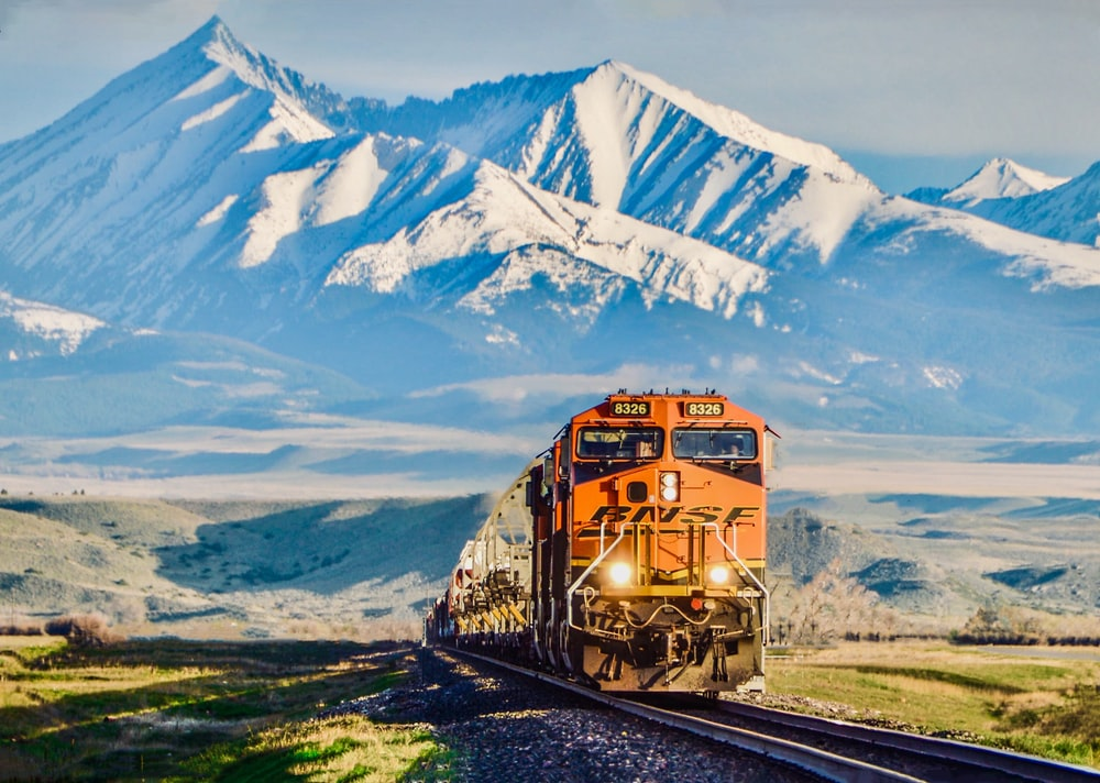 yellow train on green grass field near snow covered mountain during daytime