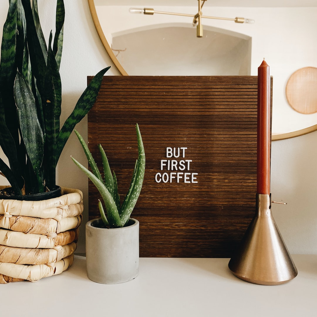 but first coffee letter board sign with candle stick and plants with round mirror and hanging west elm light in the background