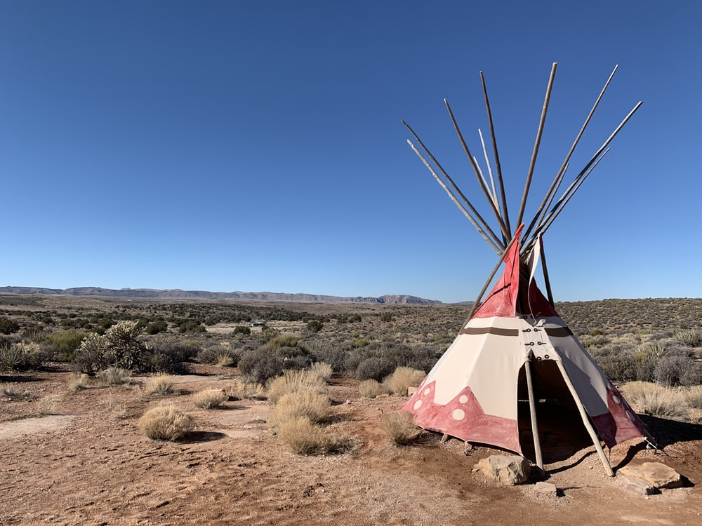 brown tent on brown field under blue sky during daytime