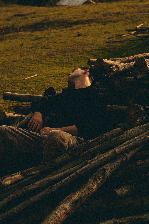 man in black jacket and gray pants sitting on brown wood log