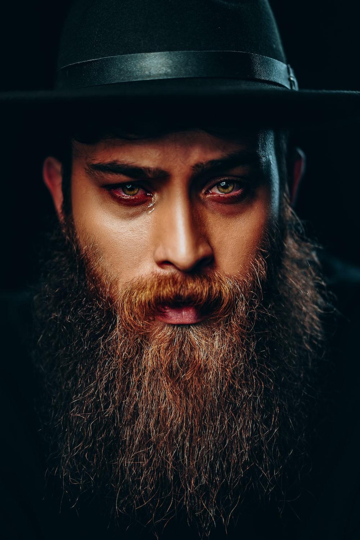 man with black beard wearing black hat