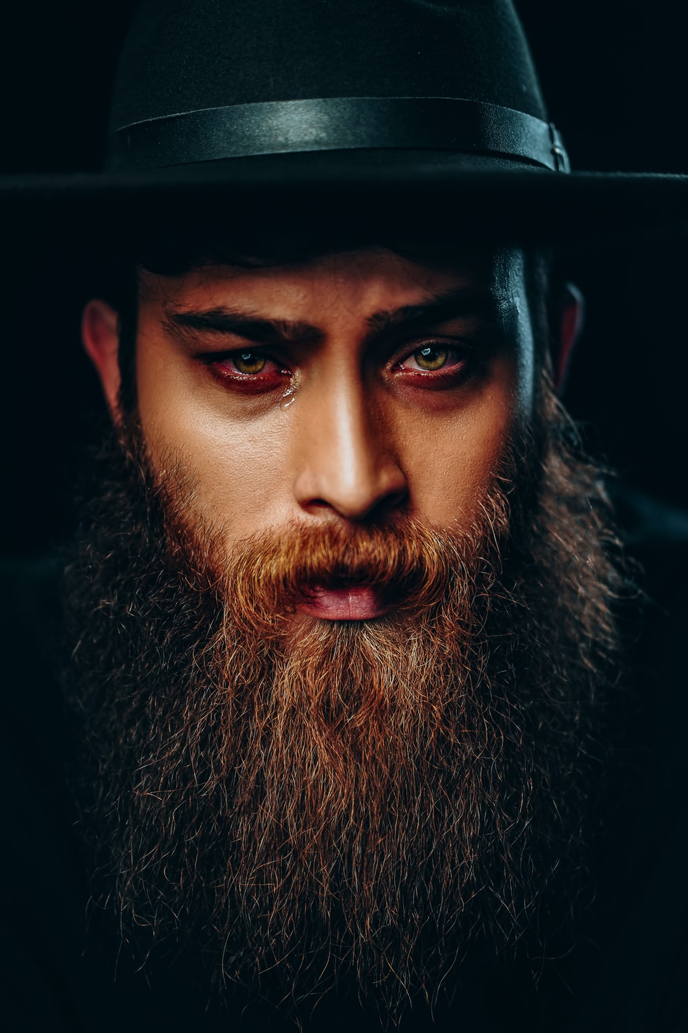 man with black beard wearing black hat