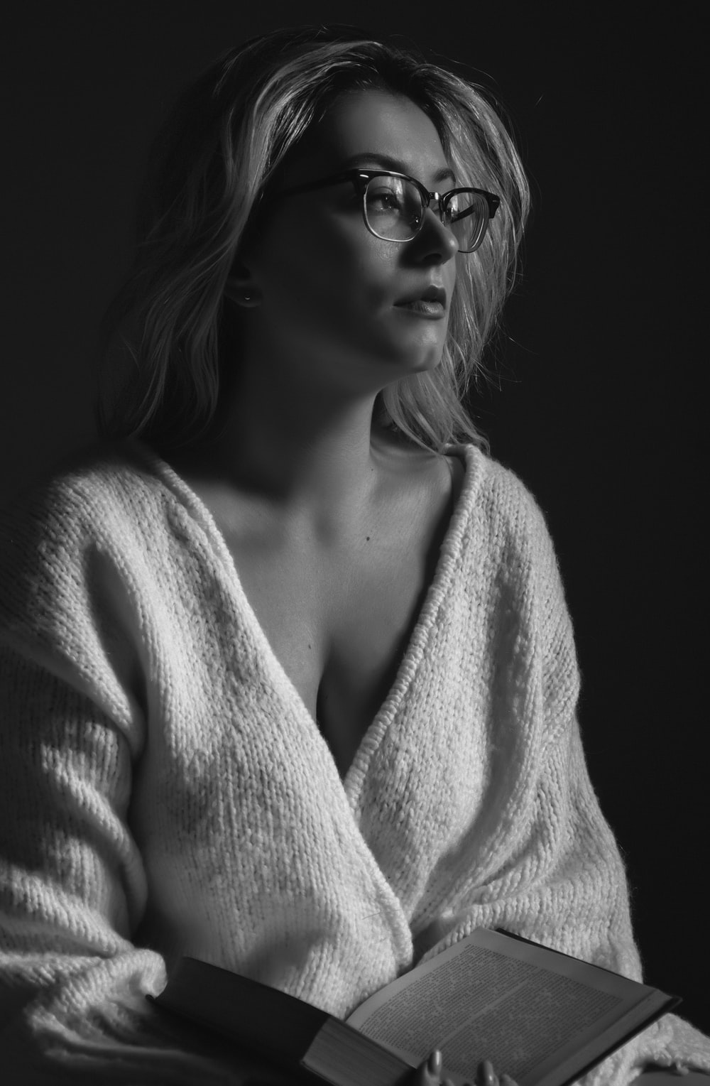 woman in white knit sweater wearing black sunglasses