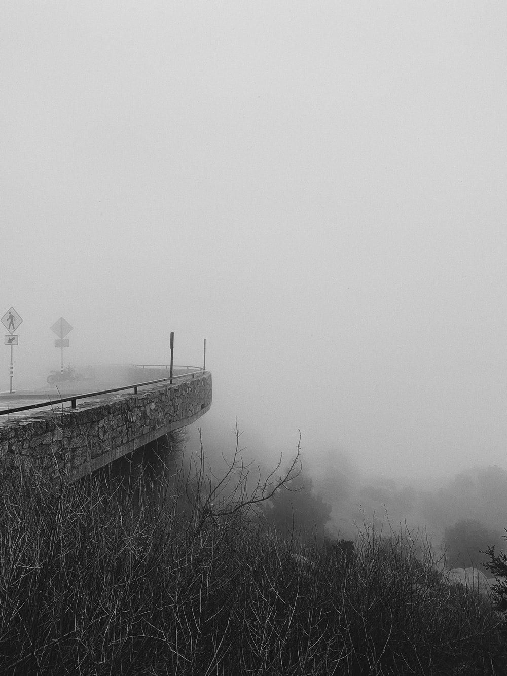 grayscale photo of person standing on bridge