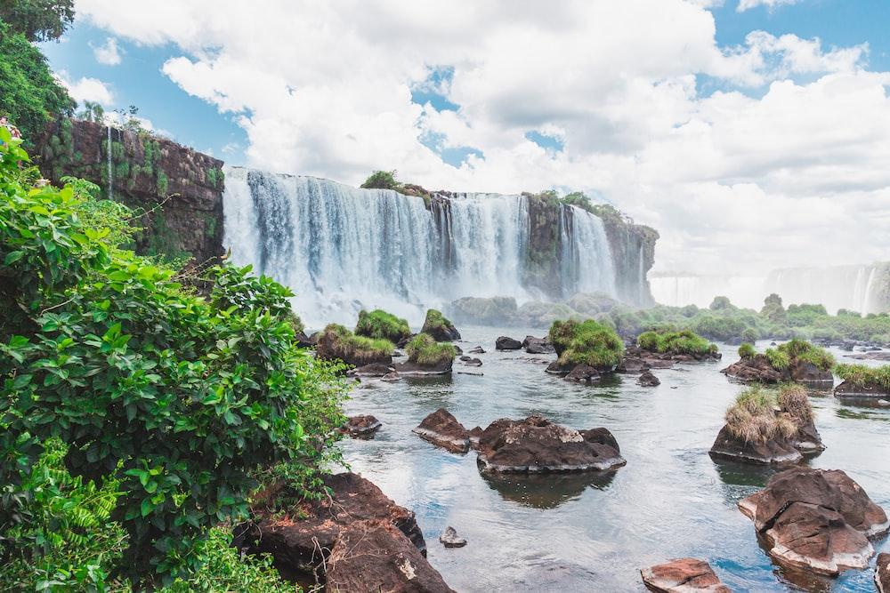 waterfalls under white clouds during daytime