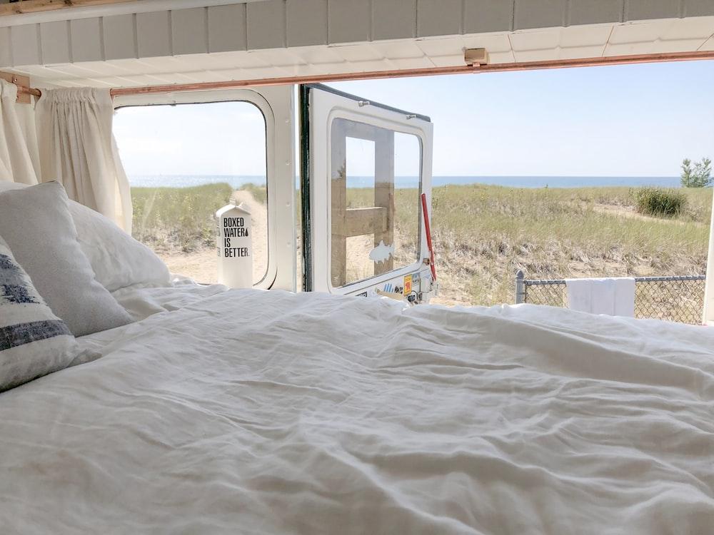 white bed linen near red metal frame