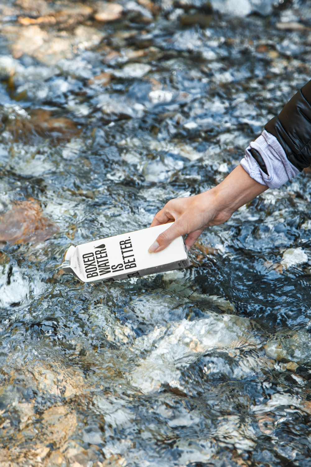 person holding white card on water