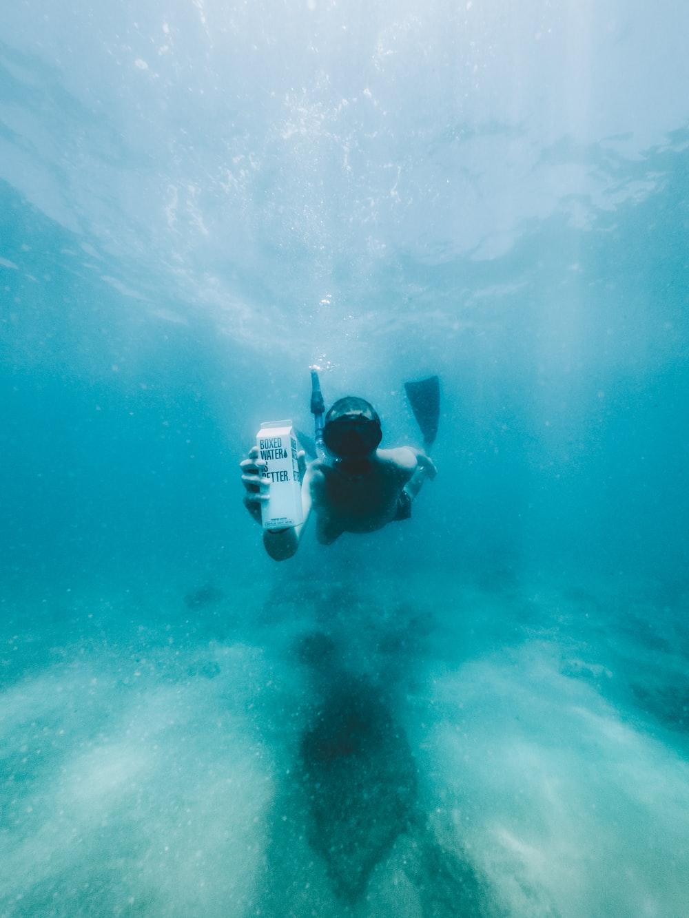 man in black diving suit under water