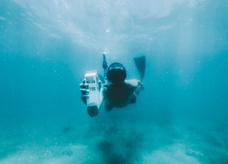 man in black diving suit under water
