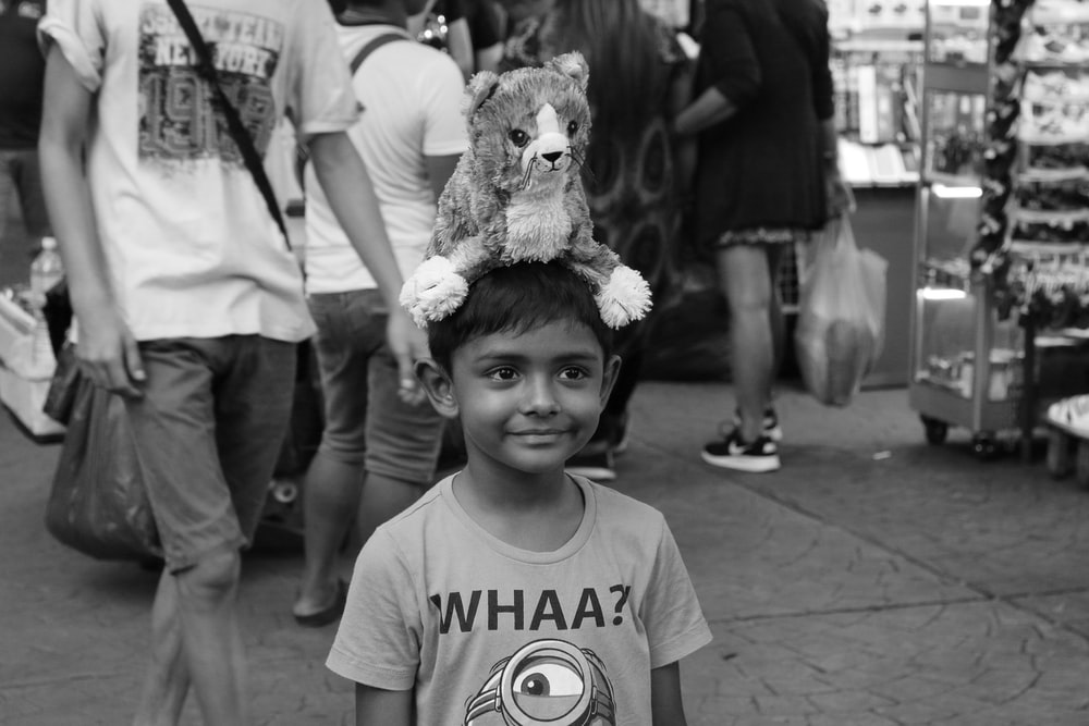 grayscale photo of girl holding bear plush toy