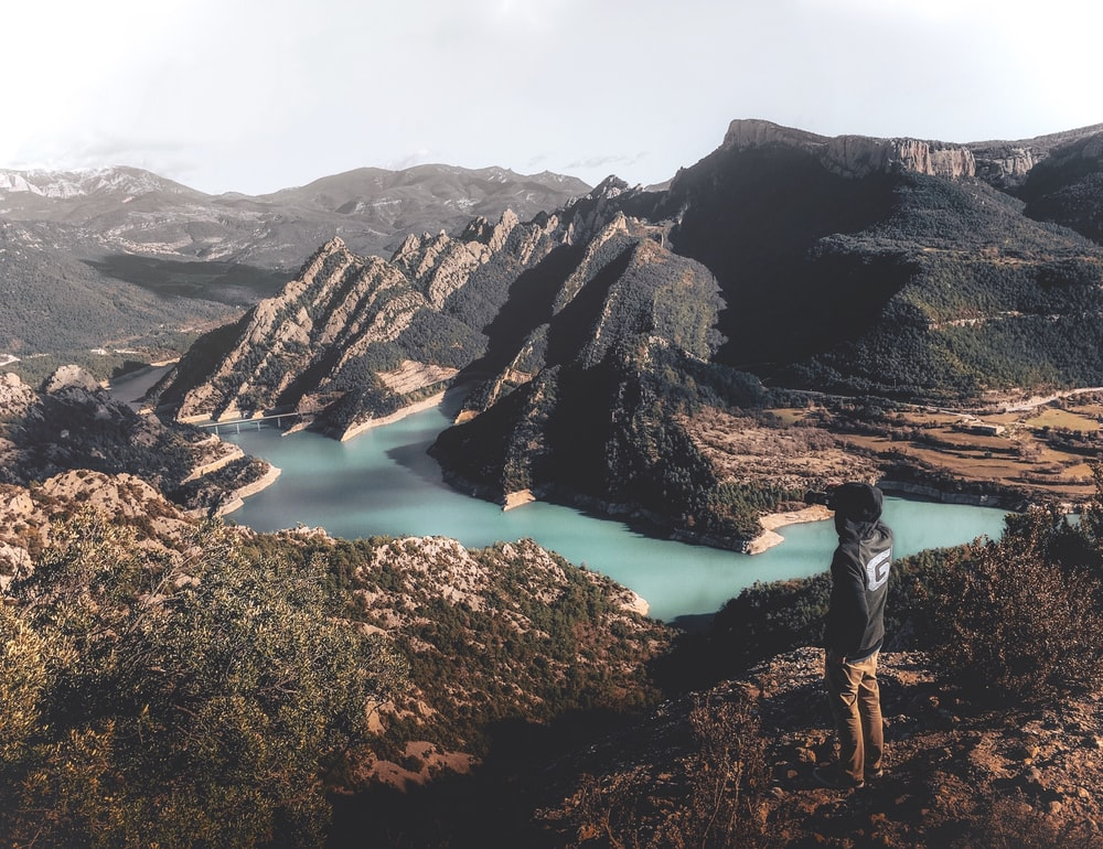 man in white shirt and black pants standing on brown rock formation near lake during daytime