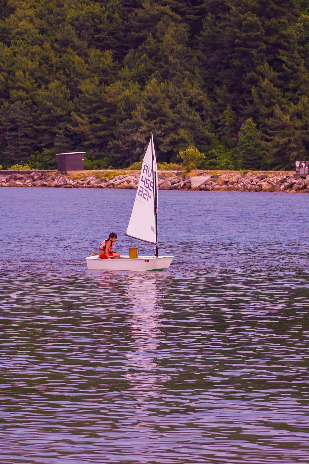 person riding on white and yellow boat on body of water during daytime