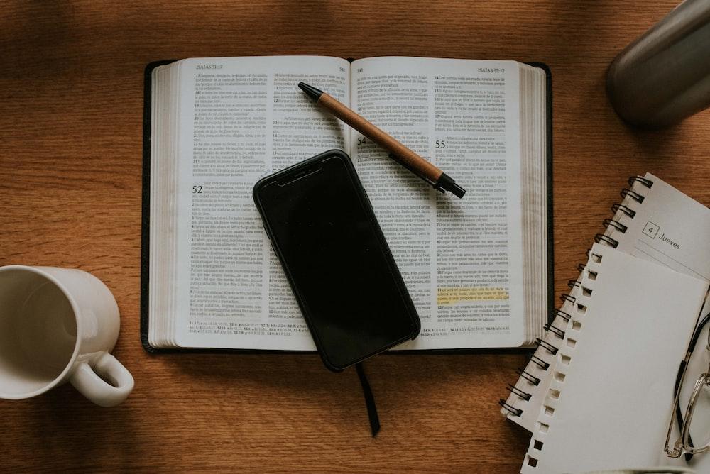 black smartphone on white notebook