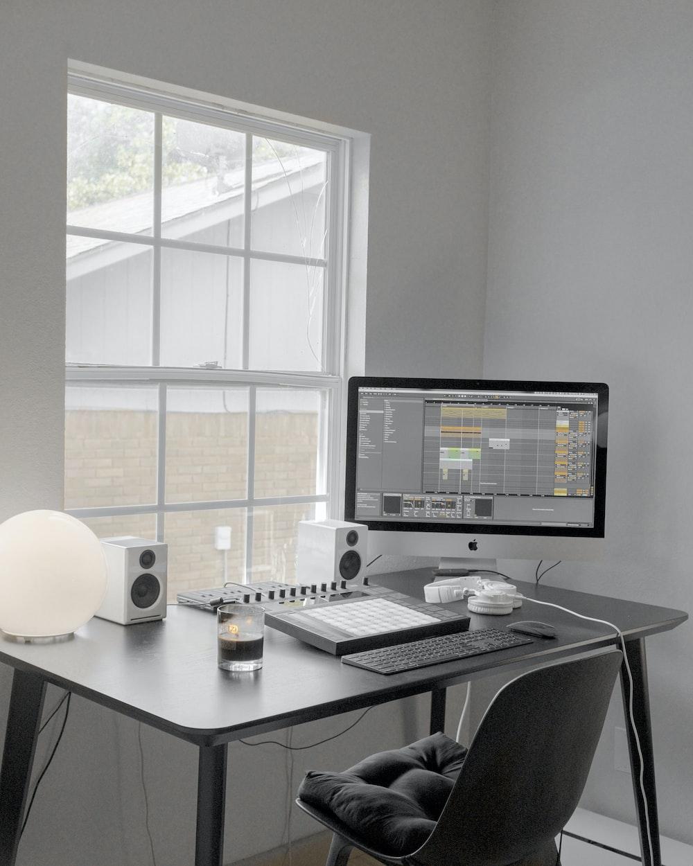 black flat screen computer monitor on white wooden desk