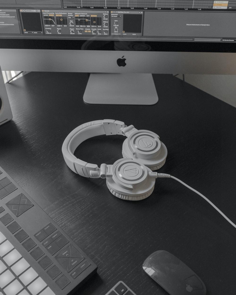 white and black headphones on black table
