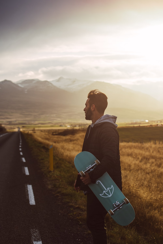 man in black jacket and blue denim jeans sitting on black skateboard on road during daytime