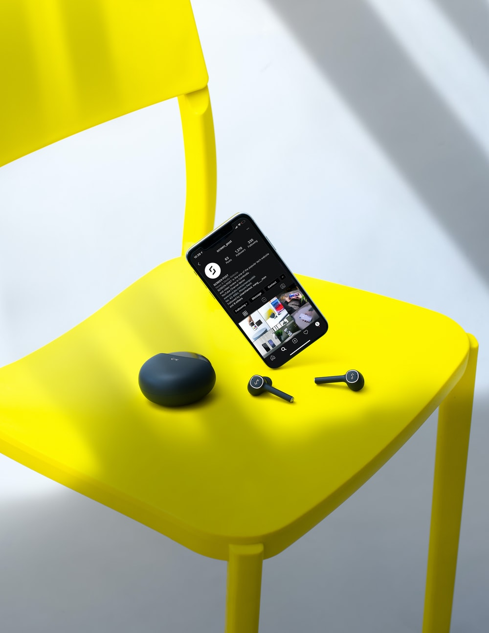 black iphone 4 on yellow chair