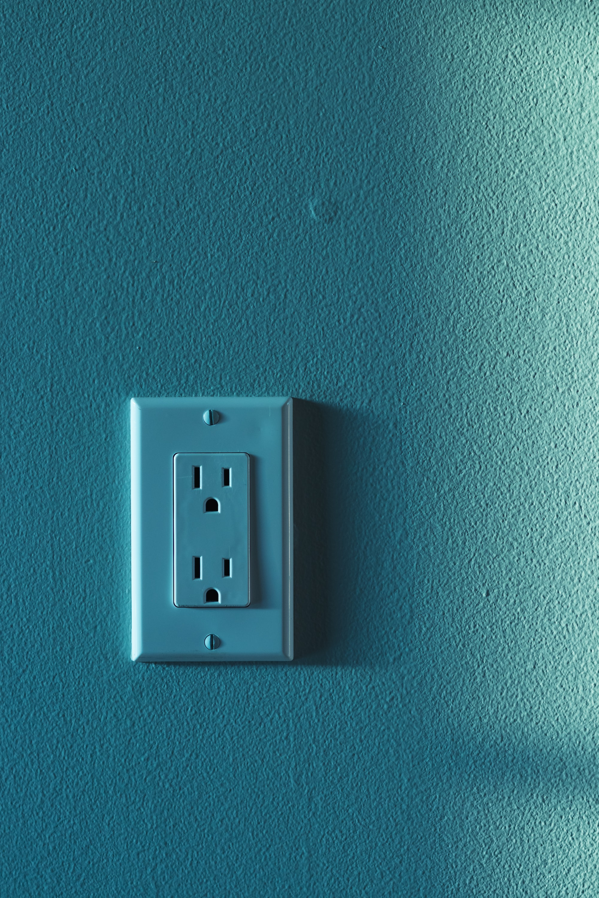 An electrical outlet in a wall, with a standard three-prong layout.