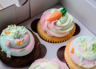 cupcakes with white icing and green and pink icing on top