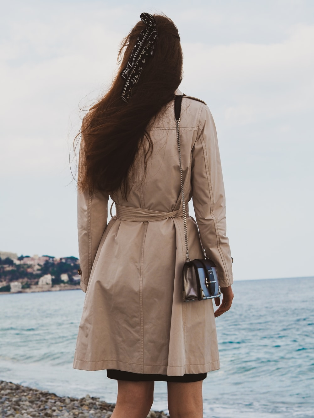 woman in brown coat standing near sea during daytime