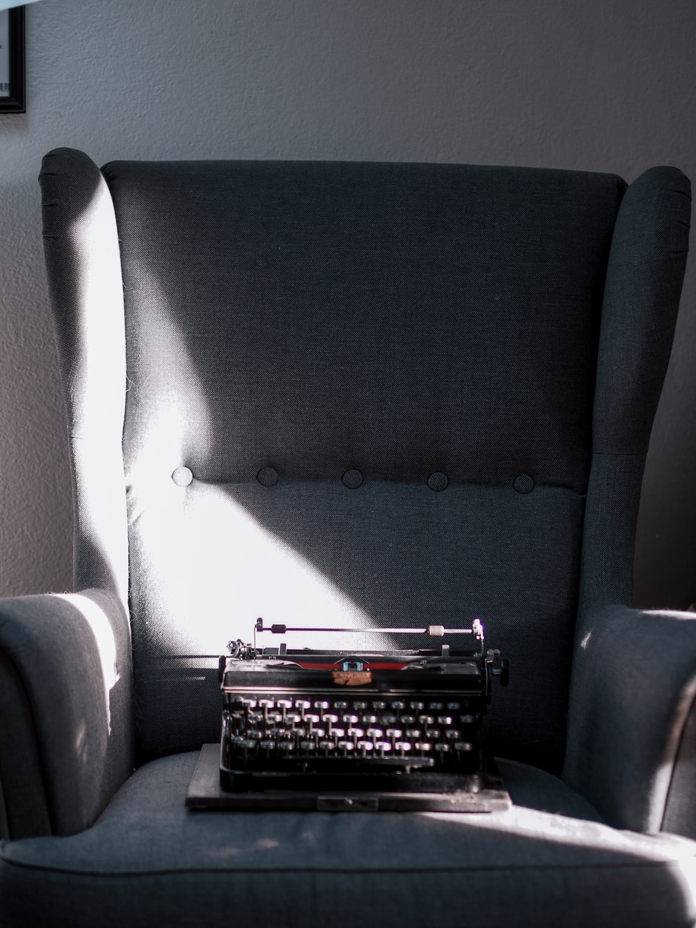 black and gray braille typewriter on gray sofa