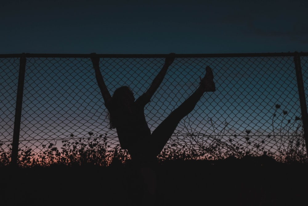 silhouette of woman jumping on trampoline