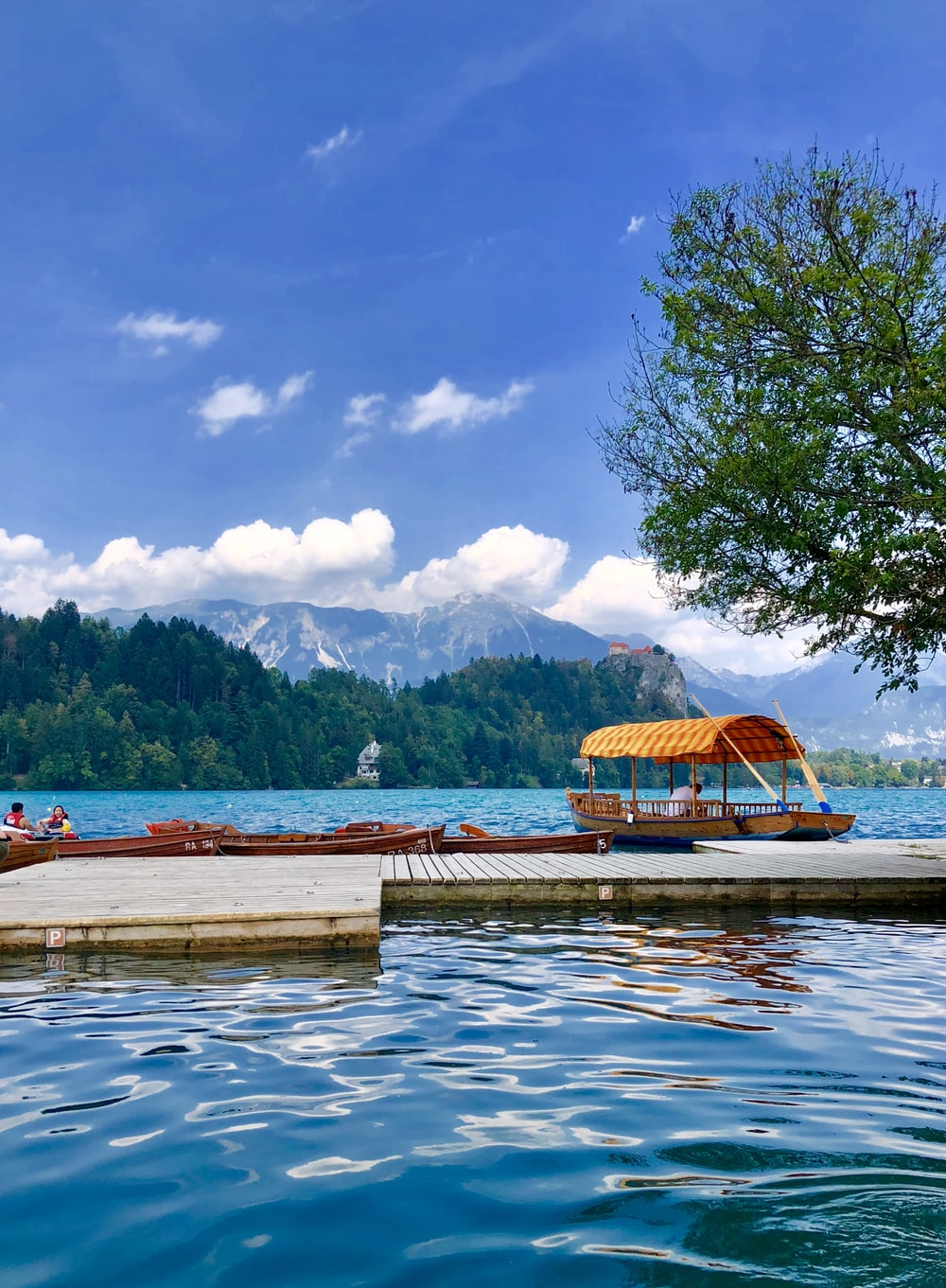 brown wooden dock on lake near green mountain under blue sky and white clouds during daytime