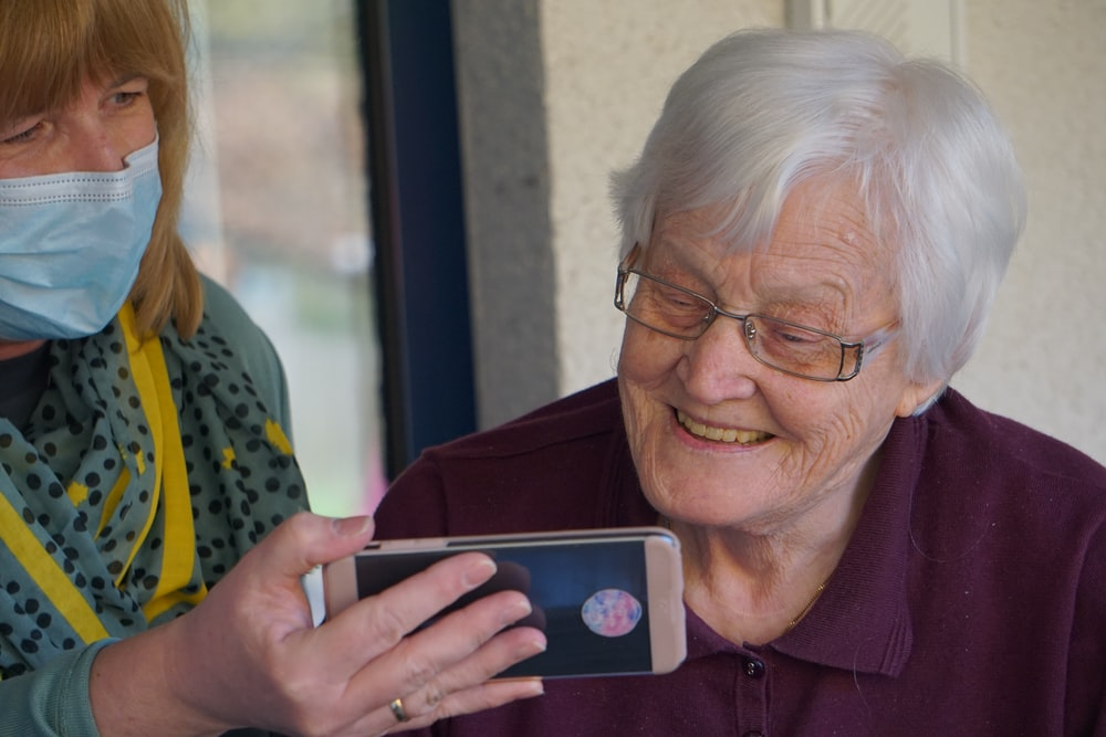 woman in brown button up shirt holding white smartphone