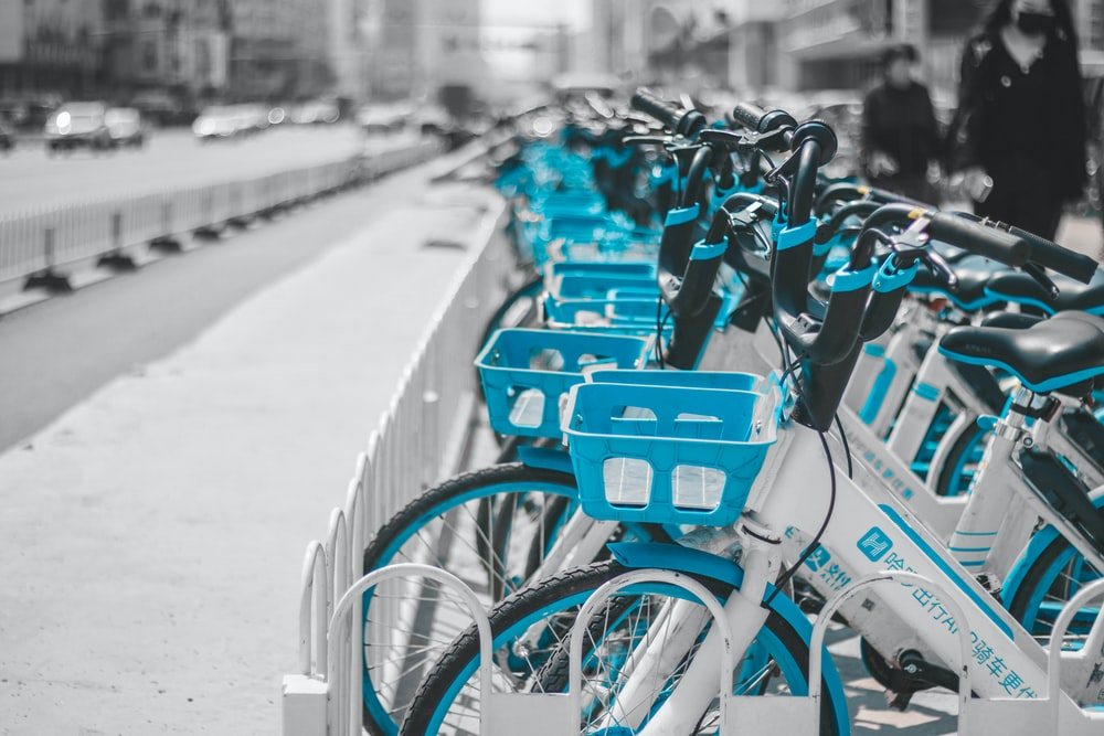 blue and black bicycles parked on sidewalk during daytime