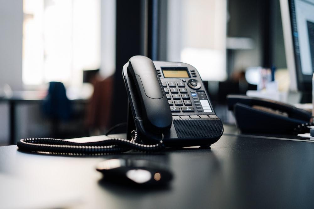 black ip desk phone on black wooden table