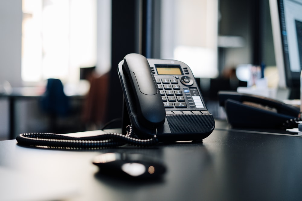 black ip desk phone on black wooden table